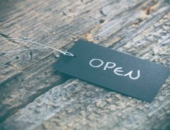 "Closeup of pricing tag with twine and ""Open"" text on wooden background"